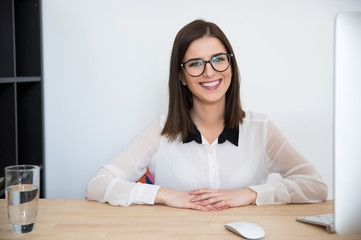 Cheerful businesswoman sitting at the table in office