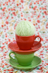 Two colorful cups and balls of yarn on a background