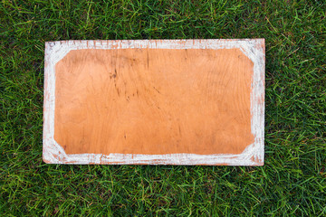Wooden sign on the grass. Blank board for your text. Spring or
