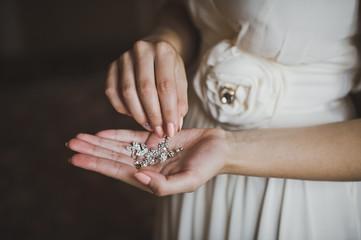 Earrings in hands of the bride 2085.