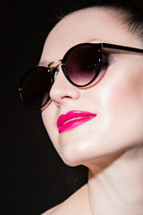 woman with pink lips and sunglasses on black background. studio