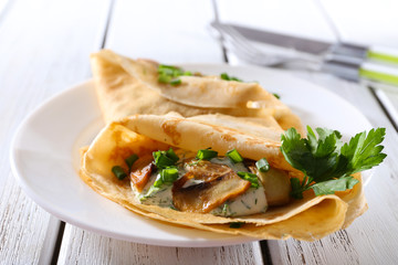 Pancakes with creamy mushrooms and greens in plate