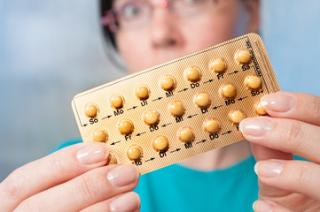 Birth control pills in hands of young woman