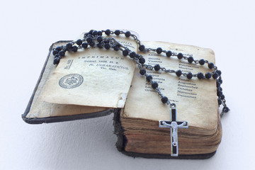 Antique prayer-book and a black rosary on it