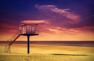 Lifeguard tower on a beach at sunset.