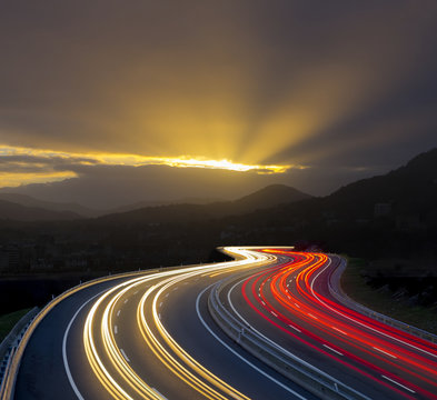 Sunset with car lights on highway