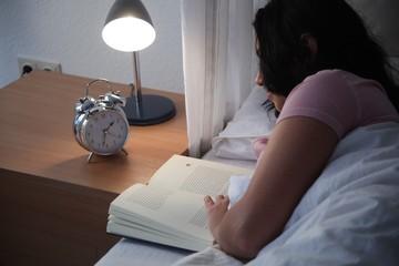 Junge Frau im Bett am lesen