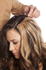 hairdresser doing his client hair with a hair extensions