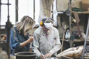 2 craftsman, woman and man talking in an artist workshop