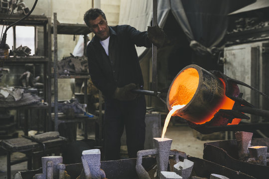 Middle aged man pouring melted bronze into molds using a crucibl