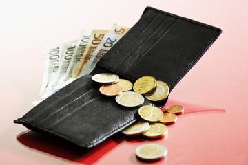 Geldbörse mit Euromünzen und Euroscheinen auf rotem Untergrund