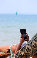 Woman in bikini on chaise-longue reading e-book by the seaside