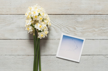 Bunch of white narcissus and printed photos on a wooden table