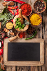 Wall Mural - Various spices on wood with blackboard