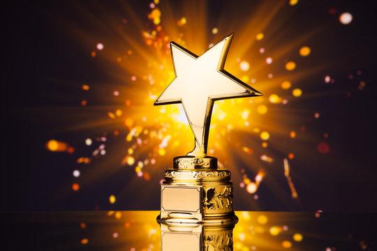 gold star trophy against shiny sparks background