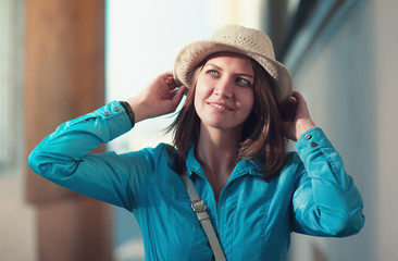 Beautiful young hipster woman in hat and blue jacket