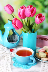Composition of spring flowers, tea and cookies