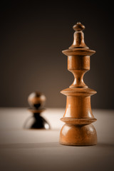 Chess. Black pawn and white king on wooden table.