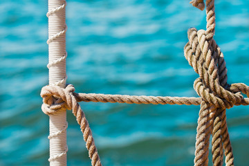 Detail of knotted ropes on a tall ship schooner at sea
