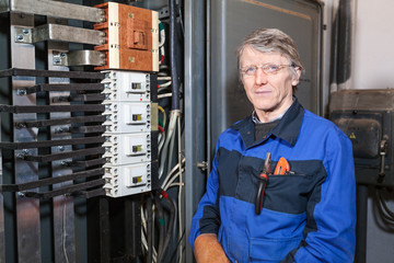 Mature electrician worker stands at work place and looking