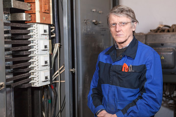 Senior electrician worker standing near high voltage panel