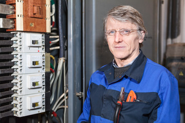 Electrician repairman in work wear stands near high voltage box