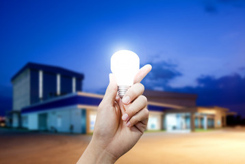 Light energy for industry, Hand holding light bulb in industrial
