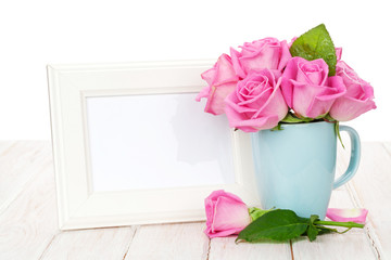 Blank photo frame and pink roses bouquet in tea cup
