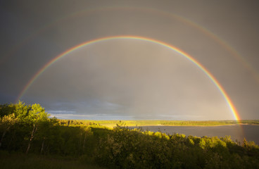 A double rainbow in the sky arching over the land.