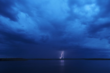 A lightning strike reflected in the water of a lake. Dark stormy dramatic sky.