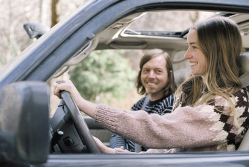 Smiling young couple driving in their car.