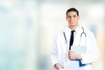 happy confident medical doctor standing in hospital hallway