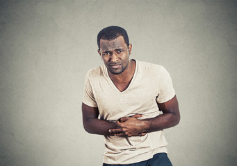 Man with stomach pain on gray wall background