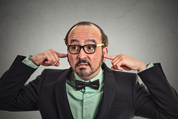 Annoyed mature man with glasses plugging ears with fingers