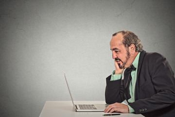Man working reading something on his laptop computer