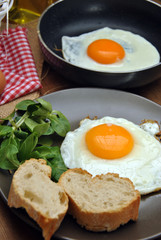 Fried eggs with plate, bread, and oilcan