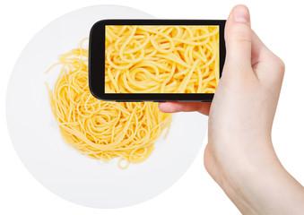 tourist photographs of spaghetti al burro on plate