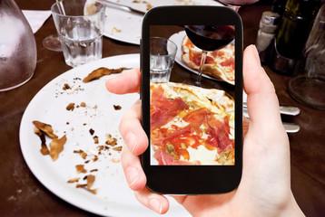 tourist photographs italian pizza with parma ham
