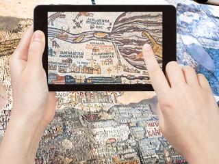 tourist shoots photo ancient byzantine Madaba map