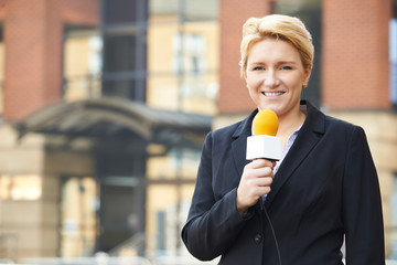 Female Journalist Broadcasting Outside Office Building