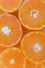 Conceptual background pattern of sliced juicy clementines