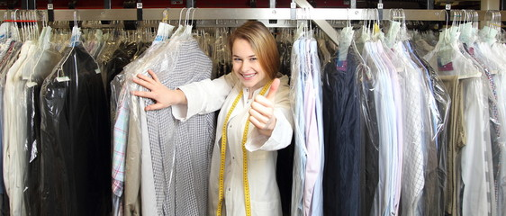 Mitarbeiterin einer Textilreinigung zwischen Hemden