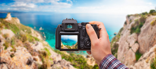 DSLR camera in hand shooting seascape