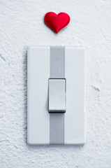 close up of white light switch with a red heart above