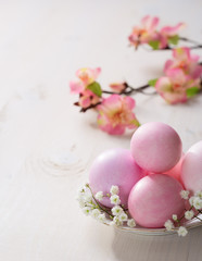 Plate  with pink   Easter eggs on wooden table.