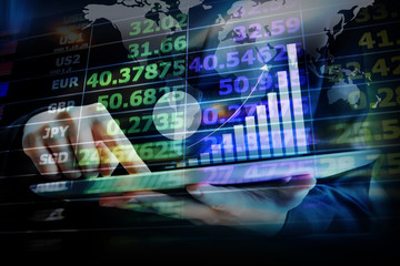 Business woman are checking exchange rates by using digital tabl