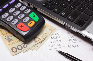 Payment terminal, money, laptop and financial calculations