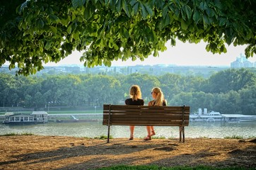 Two Women Sitting On Bench In Front Danube Rivers, Belgrade