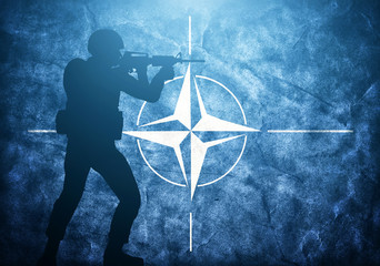 Soldier on grunge NATO flag. United army, military concept.