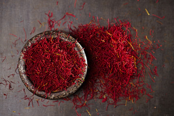 saffron spice threads and powder  in vintage iron dish